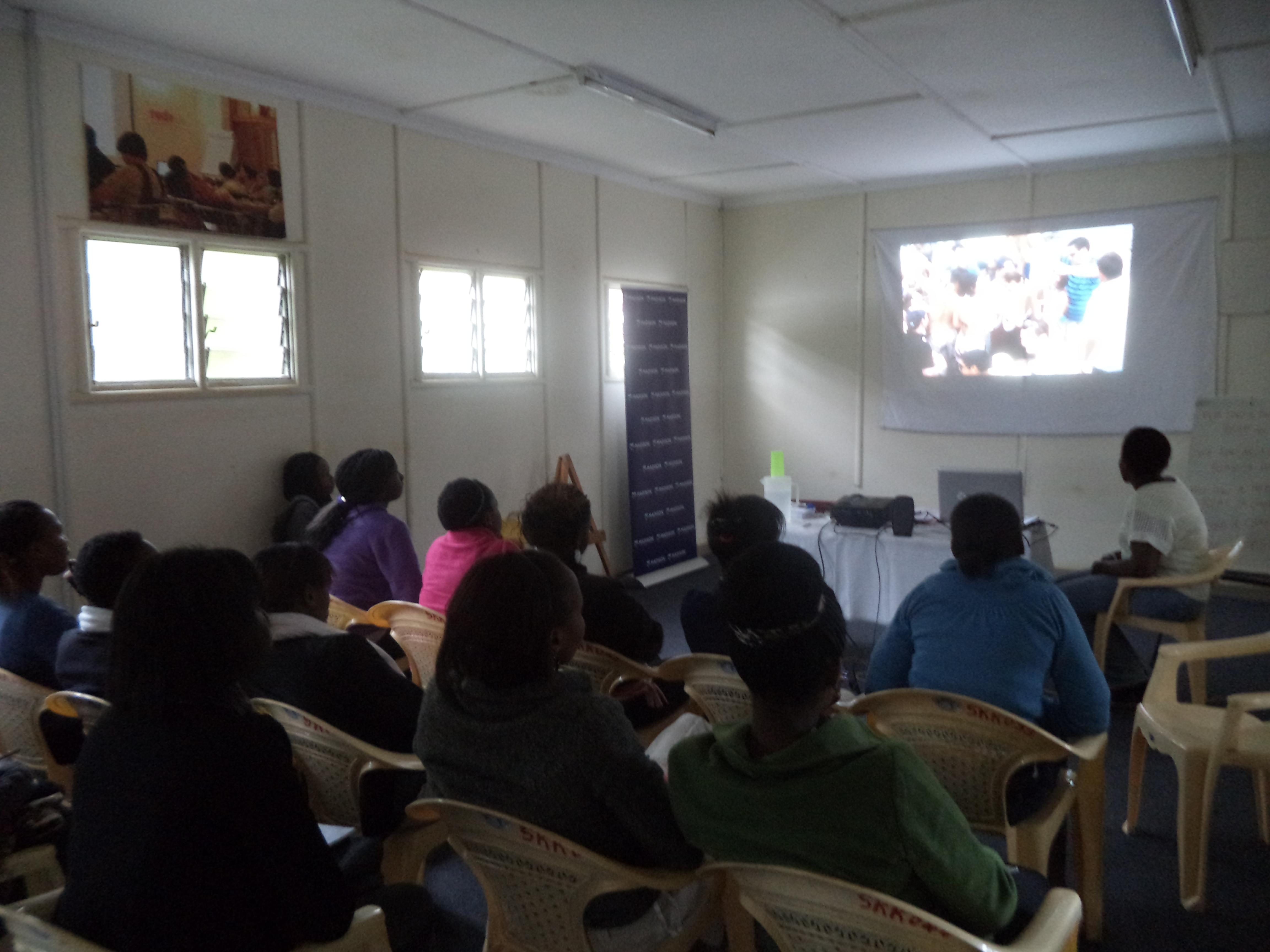 Participants watching a video during sex ed class with facilitator Caroline Kabari